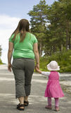 Mother and child walking. Obese mother walking with her daughter Royalty Free Stock Images
