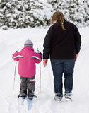Mother and child walking. Obese mother walking next to her child, who is learning to ski Royalty Free Stock Photo