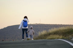 Mother and child walking away Stock Images