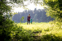 Mother and child walking in lush green countryside Stock Photo