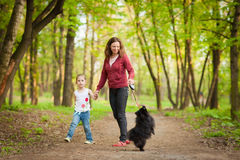 Mother and child walking playing with dog Royalty Free Stock Photo
