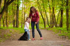 Mother and child walking playing with dog Stock Photography