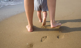 Mother and child walking on a sandy beach Stock Photos