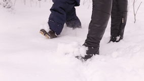 Mother with child walking on snow in winter Park, closeup of feet. stock video