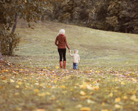 Mother and child walking together in autumn park Royalty Free Stock Photo