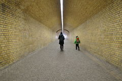 Mother and child walking through an underpass. Mother and child walking through a covered underpass or subway with brick wall, arched ceiling and illuminated Stock Images