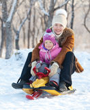 Mother with child walking in a winter park. Family walking in a winter park. Parents with child on sled Royalty Free Stock Photos