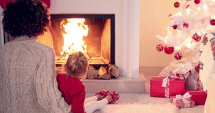 Mother and child warm up by the fireplace stock video footage