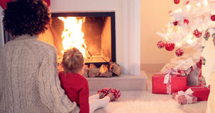 Mother and child warm up by the fireplace Royalty Free Stock Image