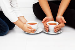 Mother with child warming hands with cup of tea. Mother with child warming hands with cup of tea on white woonen floor royalty free stock image