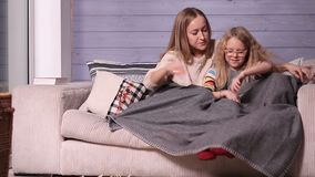Mother and child warming up under blanket at home stock video footage