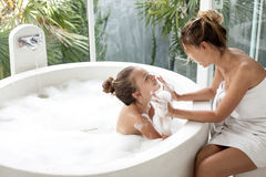 Mother with a child washing in bath. Mom washing her child in luxury hotel outdoor bath with a foam, still life Royalty Free Stock Photography