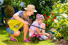 Mother and child watering flowers in garden Stock Photos
