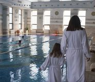 A woman with a daughter in white bathrobes around the swimming pool stock image