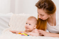 Mother and child on a white bed. Mom and baby boy in diaper playing in sunny bedroom. royalty free stock photos