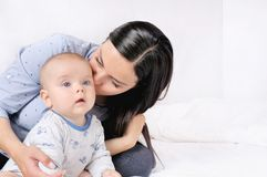 Mother and child on a white bed. Mom and baby boy playing in sunny bedroom. Family having fun together Stock Photos