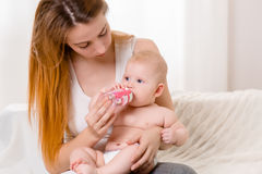 Mother and child on a white bed. Mom and baby girl in diaper playing in sunny bedroom. Royalty Free Stock Photography