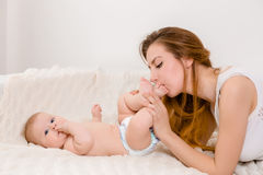 Mother and child on a white bed. Mom and baby girl in diaper playing in sunny bedroom. Royalty Free Stock Photos