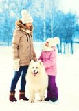 Mother and child with white Samoyed dog walking in winter Stock Photo