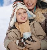 Mother and child at winter. Portrait of happy mother and child holding cup of hot tea in snow on a cold winter day laughing, smiling royalty free stock photography