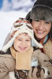Mother and child at winter. Portrait of happy mother and child holding cup of hot tea in snow on a cold winter day laughing, smiling stock photos