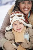 Mother and child at winter. Portrait of happy mother and child holding cup of hot tea in snow on a cold winter day laughing, smiling stock photography