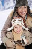 Mother and child at winter. Portrait of happy mother and child holding cup of hot tea in snow on a cold winter day laughing, smiling stock image