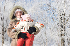 A mother and a child in a winter forest looking up Stock Images