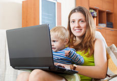 Mother with the child works with a laptop Royalty Free Stock Photos