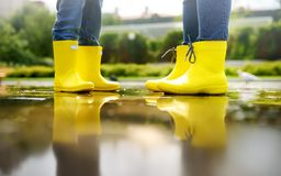 Mother and child in yellow boots playing in a puddle on a summer day royalty free stock photos