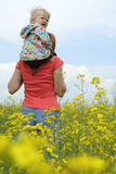 Mother with child on a yellow field Stock Images