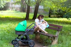 Mother and child, young mom is parenting her little toddler, woman breastfeeding and holding her baby, sitting on a park bench stock photos