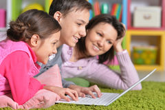 Mother with childre using laptop Stock Images
