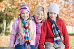 Mother and children on autumn walk. Sitting on fence Stock Photography
