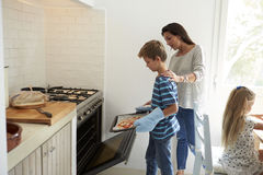 Mother And Children Baking Homemade Pizza In Oven Royalty Free Stock Photo