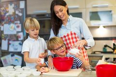 Mother and children baking together. In a kitchen at homen Royalty Free Stock Photos
