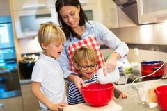 Mother and children baking together. In a kitchen at homen Royalty Free Stock Photo