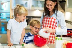 Mother and children baking together. In a kitchen at homen Stock Photography