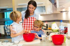 Mother and children baking together. In a kitchen at homen Royalty Free Stock Photography