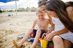 Mother and children on beach with sand bucket Stock Photo
