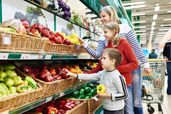 Mother and children with bell pepper in supermarket Stock Photos