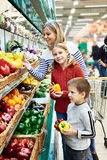 Mother and children with bell pepper in supermarket Stock Photography