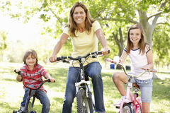 Mother and children on bikes Stock Images