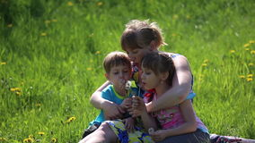 The mother with children blowing on a dandelion. Sitting in the flower meadow stock footage
