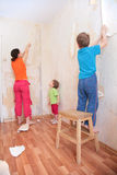 Mother with children break wallpapers from  wall Royalty Free Stock Photos