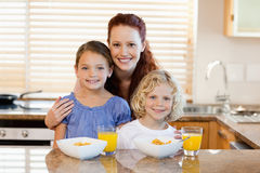Mother with children and breakfast in the kitchen Stock Photos