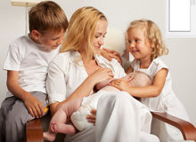 Mother with children breastfeeding her baby. Mother breastfeeding her baby at home royalty free stock images