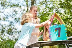 Mother and children build a puzzle house. Mother and children build a dream house out of puzzle pieces Stock Image