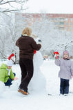 Mother and children building snowman Royalty Free Stock Photography