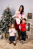 Mother with children on christmas holiday at home. Stock Images